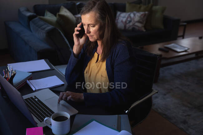 Caucasian woman enjoying time at home, social distancing and self isolation in quarantine lockdown, sitting at table, using a laptop, talking on smartphone. — Stock Photo