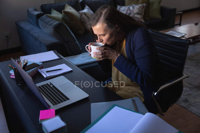 Caucasian woman enjoying time at home, social distancing and self isolation in quarantine lockdown, sitting at table, using a laptop and drinking tea. — Foto stock