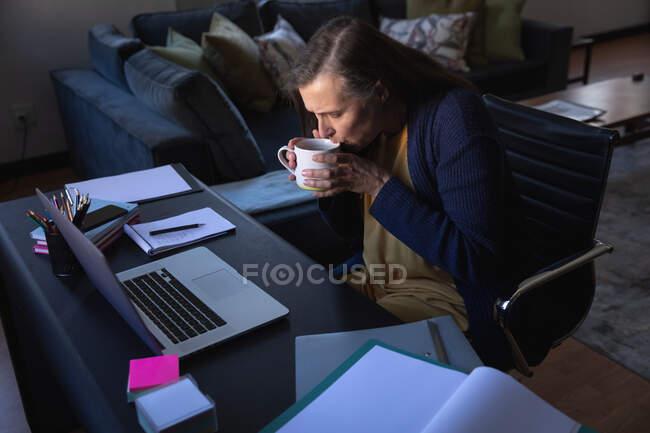 Mulher branca desfrutando de tempo em casa, distanciamento social e auto-isolamento em quarentena, sentada à mesa, usando um laptop e bebendo chá. — Fotografia de Stock