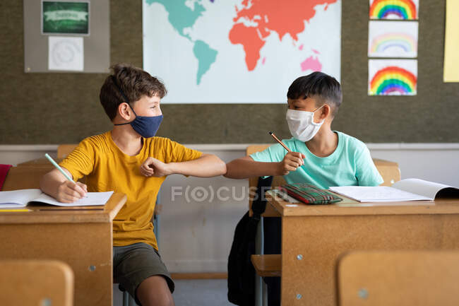 Two multi ethnic boys wearing face masks greeting each other by touching elbows in the classroom. Primary education social distancing health safety during Covid19 Coronavirus pandemic. — Stock Photo