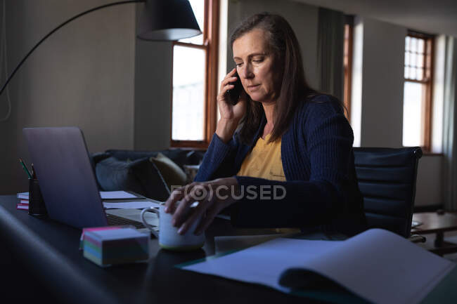 Caucasian woman enjoying time at home, social distancing and self isolation in quarantine lockdown, sitting at table, using a laptop, talking on smartphone. — Foto stock