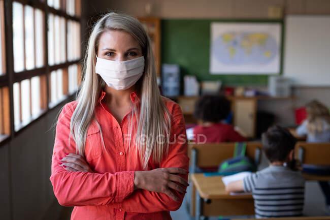 Portrait d'une enseignante caucasienne portant un masque facial, les bras croisés en classe. Enseignement primaire distanciation sociale sécurité sanitaire pendant la pandémie de coronavirus Covid19. — Photo de stock