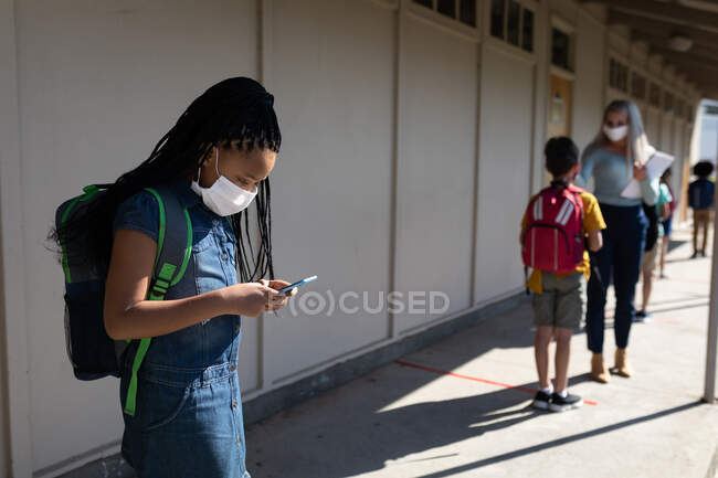 Mixed race girl wearing face mask using smartphone and teacher measuring temperature in elementary school. Primary education social distancing health safety during Covid19 Coronavirus pandemic. — Stock Photo