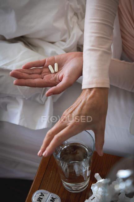 Parte média da mulher doente que passa o tempo em casa, distanciamento social e auto-isolamento em quarentena, deitada na cama, segurando pílulas, chegando à água. — Fotografia de Stock