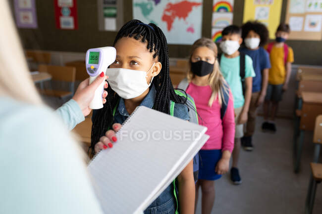 Professeure caucasienne mesurant la température des enfants dans une école primaire. Enseignement primaire distanciation sociale sécurité sanitaire pendant la pandémie de coronavirus Covid19. — Photo de stock