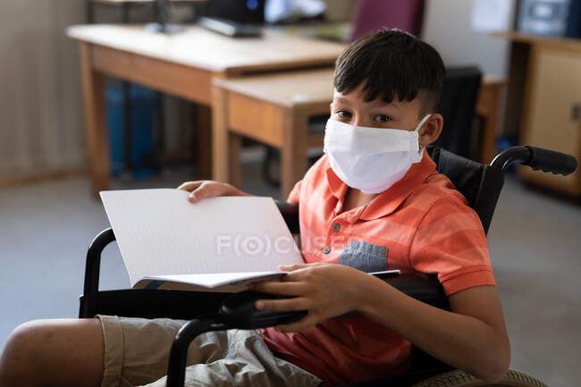 Portrait of disable mixed race boy wearing face mask, sitting in his wheelchair in the classroom. Primary education social distancing health safety during Covid19 Coronavirus pandemic. — Stock Photo