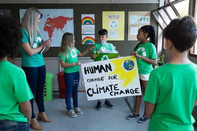 Une enseignante caucasienne et un groupe d'enfants multiethniques tenant une banderole sur le changement climatique à l'école. Enseignement primaire distanciation sociale sécurité sanitaire pendant la pandémie de coronavirus Covid19. — Photo de stock