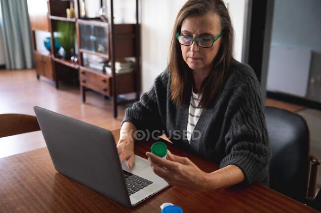 Mulher branca desfrutando de tempo em casa, distanciamento social e auto-isolamento em quarentena, sentado na sala de estar, usando computador portátil, segurando recipiente de medicação. — Fotografia de Stock