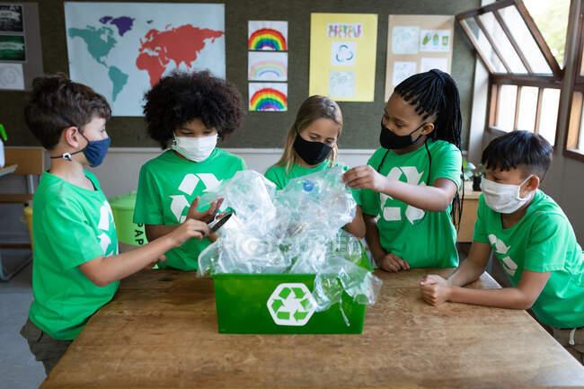 Grupo de niños multiétnicos que usan máscaras faciales con artículos de plástico en clase en la escuela. Educación primaria distanciamiento social seguridad sanitaria durante la pandemia del Coronavirus Covid19. - foto de stock
