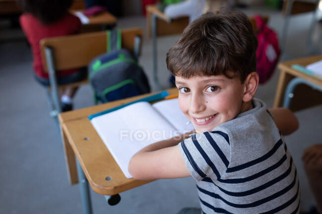 Portrait of a Caucasian boy smiling while sitting on his desk at school. Primary education social distancing health safety during Covid19 Coronavirus pandemic. — Stock Photo