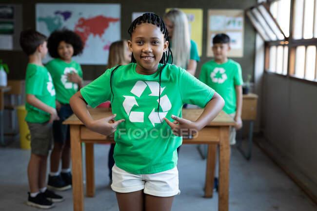 Retrato de una chica de raza mixta con camiseta de reciclaje de pie con las manos en las caderas en clase. Educación primaria distanciamiento social seguridad sanitaria durante la pandemia del Coronavirus Covid19. - foto de stock