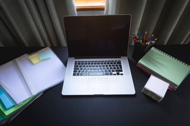 General view of home office grey desk with laptop computer, documents, pencils, notebooks, memo notes, ready for working from home during social distancing and self isolation in quarantine lockdown. — Foto stock