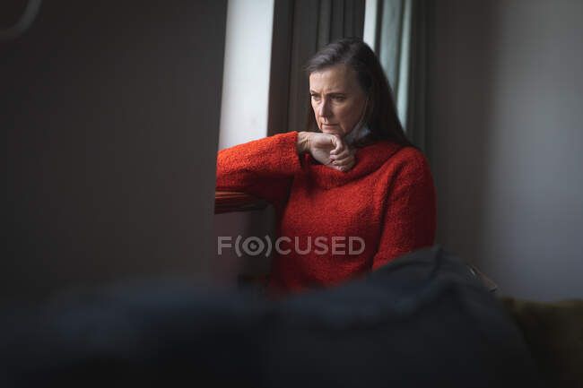 Worried Caucasian woman spending time at home, social distancing and self isolation in quarantine lockdown, with face mask protecting from Covid 19 coronavirus infection, looking out of window. — Stock Photo