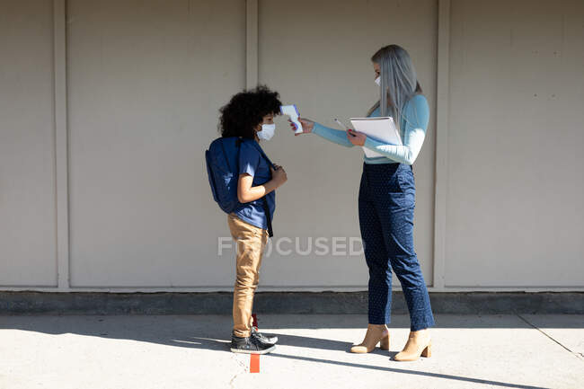 Caucasian female teacher wearing face mask measuring temperature of a boy in an elementary school. Primary education social distancing health safety during Covid19 Coronavirus pandemic. — Stock Photo