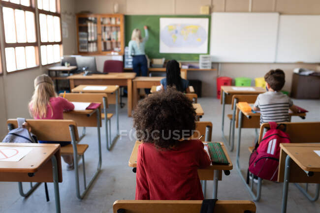 Group of multi ethnic kids sitting on their desk in the classroom during the lesson. Primary education social distancing health safety during Covid19 Coronavirus pandemic. — Stock Photo