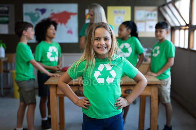 Retrato de una chica caucásica con camiseta de reciclaje de pie con las manos en las caderas en clase. Educación primaria distanciamiento social seguridad sanitaria durante la pandemia del Coronavirus Covid19. - foto de stock