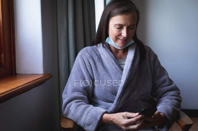 Caucasian woman spending time at home, social distancing and self isolation in quarantine lockdown, with face mask protecting from Covid 19 coronavirus infection, using smartphone. — Stock Photo
