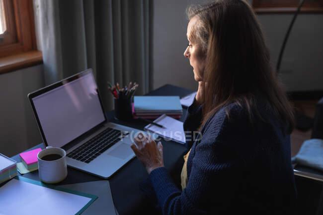 Mulher branca desfrutando de tempo em casa, distanciamento social e auto-isolamento em quarentena, sentada à mesa, usando um laptop. — Fotografia de Stock