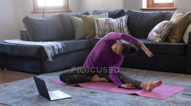 Caucasian woman enjoying time at home, social distancing and self isolation in quarantine lockdown, sitting on floor in living room with laptop, exercising, stretching. — Stock Photo
