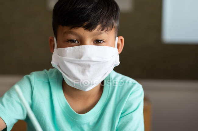 Portrait of an Asian boy sitting at desk wearing face mask in classroom. Primary education social distancing health safety during Covid19 Coronavirus pandemic. — Stock Photo