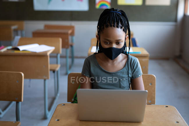 Mixed race girl wearing a face mask, using laptop while sitting on his desk in class at school. Primary education social distancing health safety during Covid19 Coronavirus pandemic. — Stock Photo