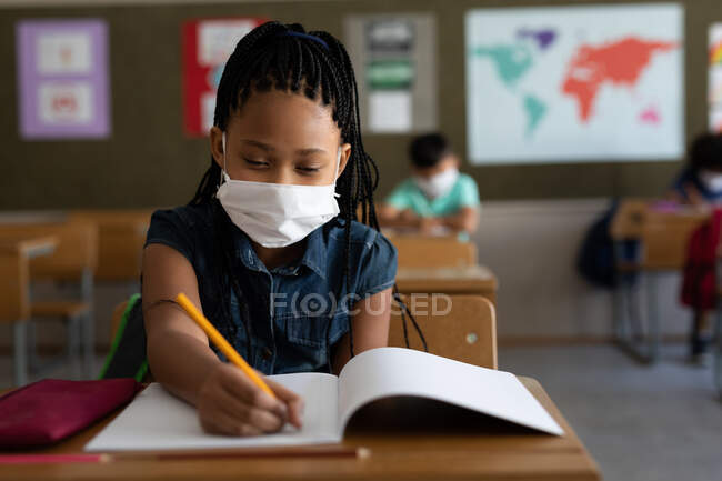 Mixed race girl sitting at desks wearing face mask in classroom. Primary education social distancing health safety during Covid19 Coronavirus pandemic. — Stock Photo