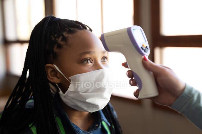 Змішана дівчина в масці обличчя отримує температуру, виміряну в початковій школі. Первинна освіта Соціальна безпека для здоров'я під час пандемії Ковіда19 Коронавірус. — стокове фото