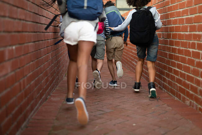 Rear low section of a group of multi ethnic kids running during a break. Primary education social distancing health safety during Covid19 Coronavirus pandemic. — Stock Photo