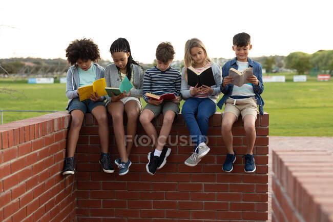 Groupe d'enfants multiethniques lisant des livres assis sur le mur pendant une pause. Enseignement primaire distanciation sociale sécurité sanitaire pendant la pandémie de coronavirus Covid19. — Photo de stock