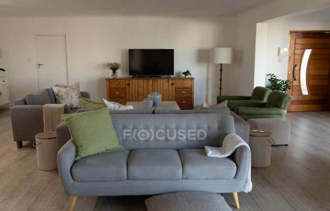 Современная, пустая гостиная с двумя серыми и одним зеленым диванами, большим экраном телевизора и ежедневными гаджетами, лежащими в современном доме — стоковое фото