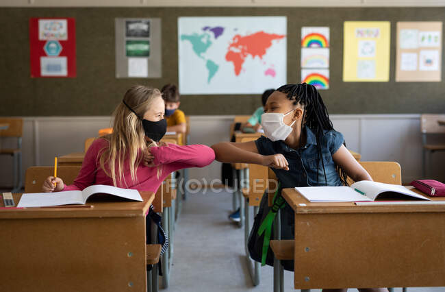 Two multi ethnic girls wearing face masks greeting each other by touching elbows in the classroom. Primary education social distancing health safety during Covid19 Coronavirus pandemic. — Stock Photo