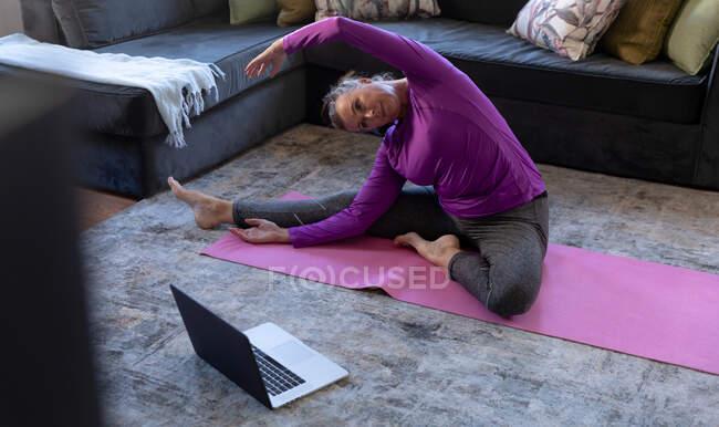 Mulher branca desfrutando de tempo em casa, distanciamento social e auto-isolamento em quarentena, sentada no chão na sala de estar com laptop, exercício, alongamento. — Fotografia de Stock