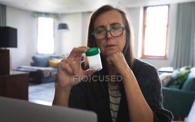 Mulher branca desfrutando de tempo em casa, distanciamento social e auto-isolamento em quarentena, sentado na sala de estar, segurando recipiente de medicação vazio. — Fotografia de Stock