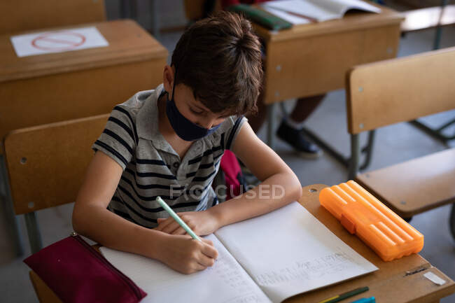 Caucasian boy wearing face mask, sitting on his desk during the lesson. Primary education social distancing health safety during Covid19 Coronavirus pandemic. — Stock Photo