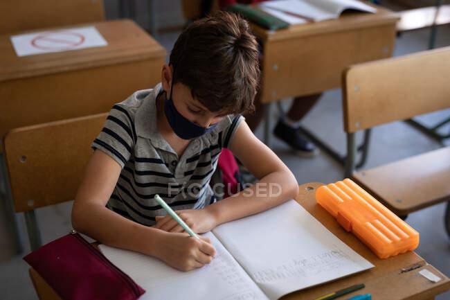 Белый мальчик в маске, сидит на столе во время урока. Начальное образование Социальное дистанцирование безопасности здоровья во время пандемии Coronavirus Covid19. — стоковое фото