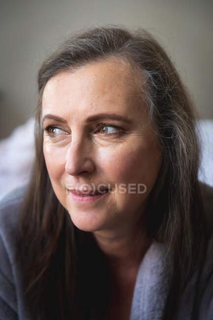 Близко к счастливой белой женщине с длинными темными волосами, наслаждающейся временем дома, социальной дистанцированностью и самоизоляцией в карантинной изоляции, улыбающейся. — стоковое фото