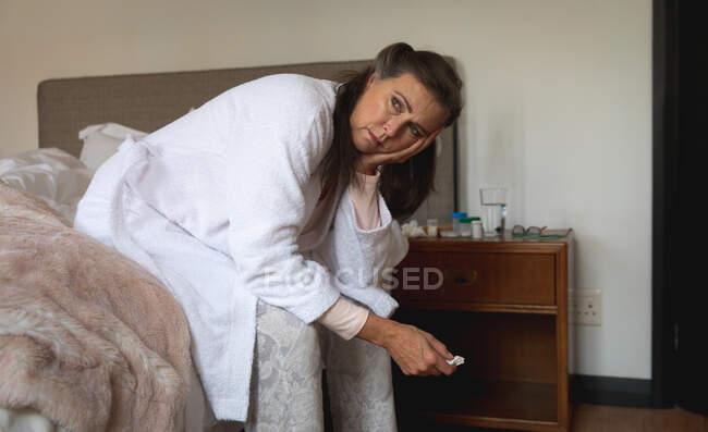 Больная белая женщина проводит время дома, социальное дистанцирование и самоизоляция в карантинной изоляции, сидя на кровати, держа в руках ткани. — стоковое фото