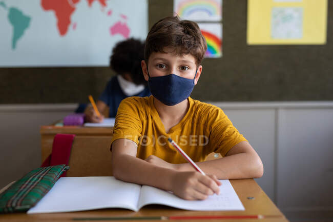Two multi ethnic children sitting at desks wearing face masks in classroom. Primary education social distancing health safety during Covid19 Coronavirus pandemic — Stock Photo