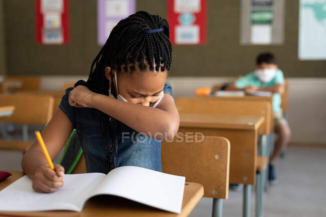 Mixed race girl sitting at desk wearing face mask in classroom, covering her face while sneezing. Primary education social distancing health safety during Covid19 Coronavirus pandemic. — Stock Photo