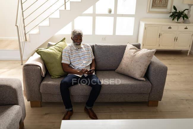 Afro-americano idoso sentado em um sofá, usando um smartphone, distanciamento social e auto-isolamento em quarentena bloqueio — Fotografia de Stock
