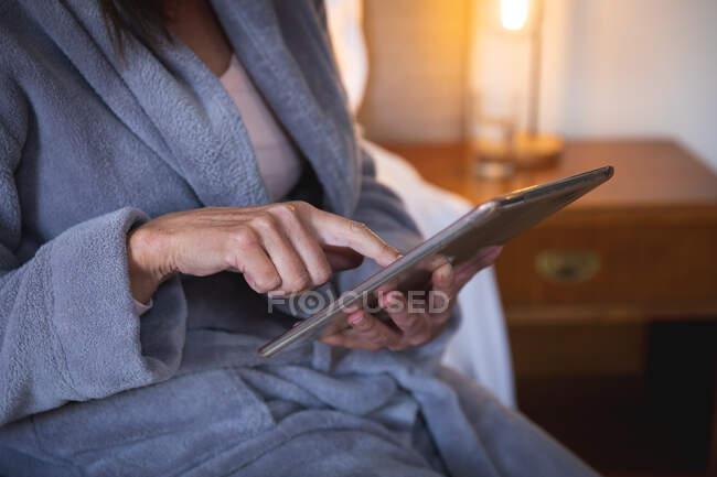 Parte média da mulher desfrutando de tempo em casa, distanciamento social e auto-isolamento em quarentena, sentada na cama no quarto, usando um tablet digital. — Fotografia de Stock