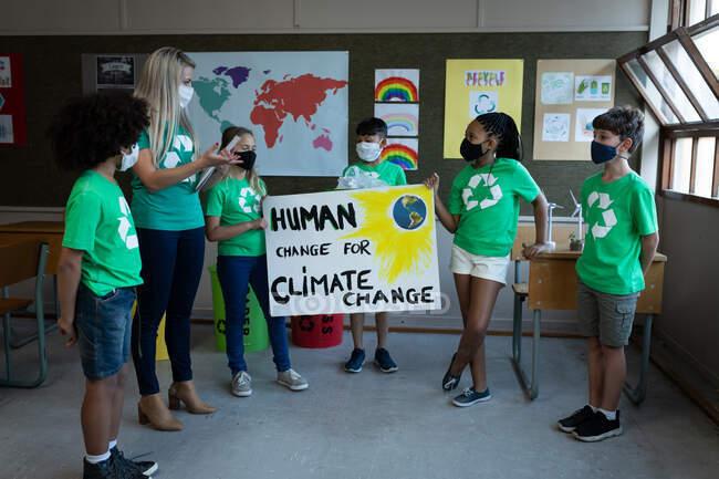 Maestra caucásica y grupo de niños multiétnicos que usan máscaras faciales y sostienen pancartas sobre el cambio climático en la escuela. Educación primaria distanciamiento social de la seguridad sanitaria durante el Covid19 Coronavirus. - foto de stock