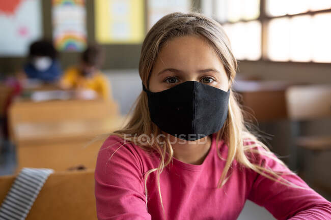 Portrait of Caucasian girl sitting at desks wearing face mask in classroom. Primary education social distancing health safety during Covid19 Coronavirus pandemic. — Stock Photo
