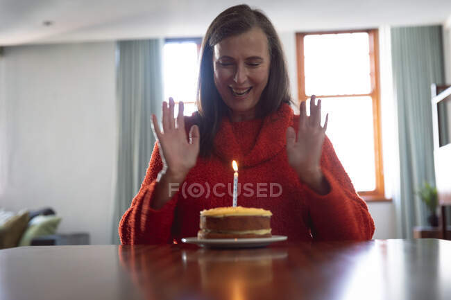 Happy Caucasian woman spending time at home, social distancing and self isolation in quarantine lockdown, sitting alone at a table with birthday cake with one candle. — Foto stock