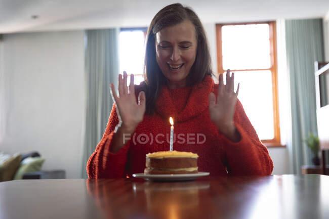 Mulher caucasiana feliz passar o tempo em casa, distanciamento social e auto-isolamento em quarentena lockdown, sentado sozinho em uma mesa com bolo de aniversário com uma vela. — Fotografia de Stock
