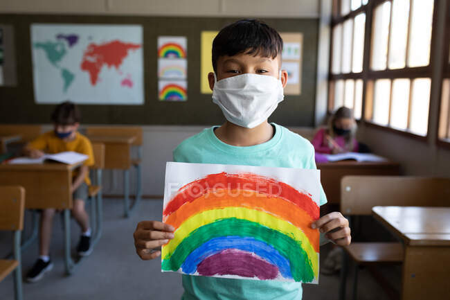 Portrait of a mixed race boy wearing face mask holding a rainbow drawing in the classroom. Primary education social distancing health safety during Covid19 Coronavirus pandemic. — Stock Photo