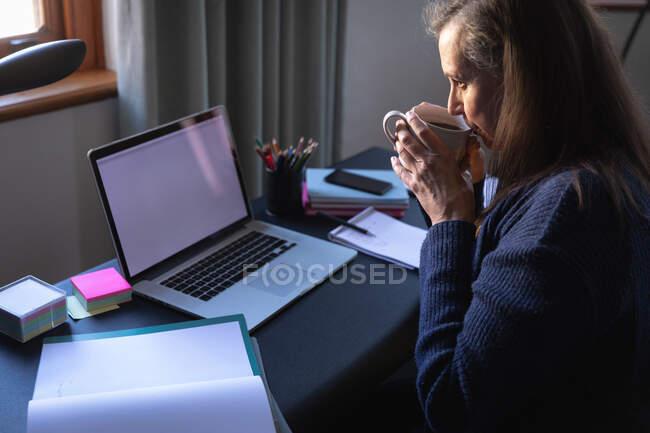 Mulher branca desfrutando de tempo em casa, distanciamento social e auto-isolamento em quarentena, sentada à mesa, usando um laptop, bebendo café. — Fotografia de Stock