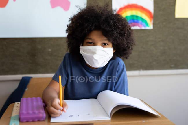 Portrait d'un garçon de race mixte assis au bureau portant un masque facial en classe. Enseignement primaire distanciation sociale sécurité sanitaire pendant la pandémie de coronavirus Covid19. — Photo de stock