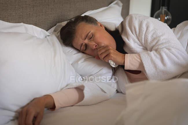 Больная белая женщина проводит время дома, социальное дистанцирование и самоизоляция в карантинной изоляции, лежит в постели, кашляет. — стоковое фото