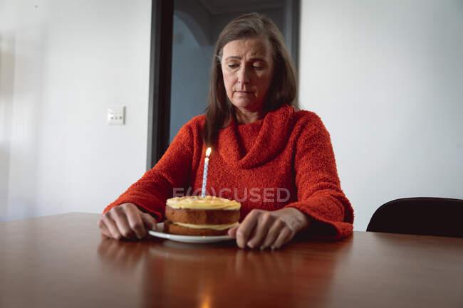 Грустная белая женщина, проводящая время дома, социальное дистанцирование и самоизоляция в карантинной изоляции, сидящая одна за столом с праздничным тортом с одной свечой. — стоковое фото